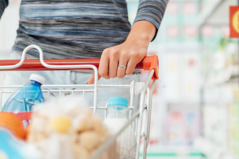 Shopping at the supermarket. Woman doing grocery shopping at the supermarket and pushing a full shopping cart, hand detail close up, lifestyle concept stock photography