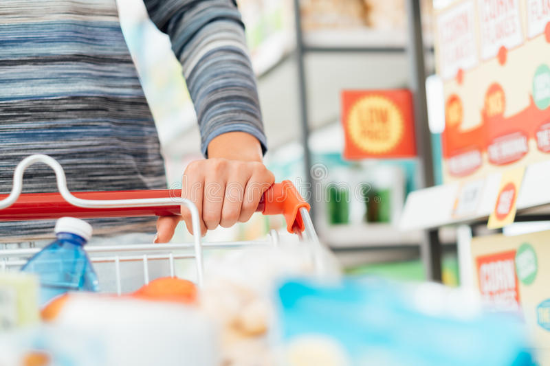 Shopping at the supermarket. Woman doing grocery shopping at the supermarket and pushing a full shopping cart, hand detail close up, lifestyle concept stock image