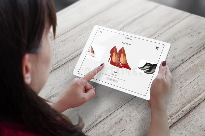 Shopping with tablet. Woman buy red shoes on online market stock image