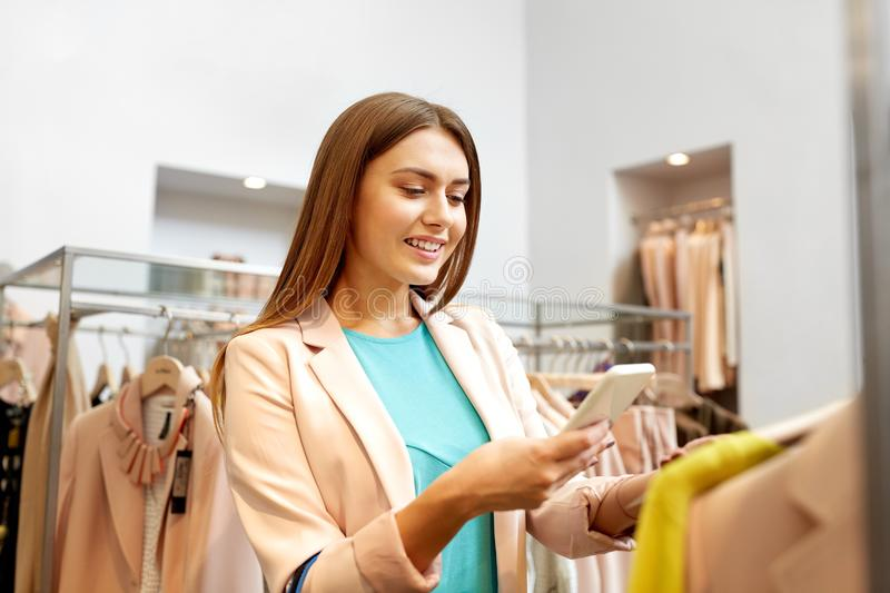 Happy woman using phone app at clothing store. Shopping, technology and people concept - happy young woman choosing clothes in mall or clothing store and taking royalty free stock images