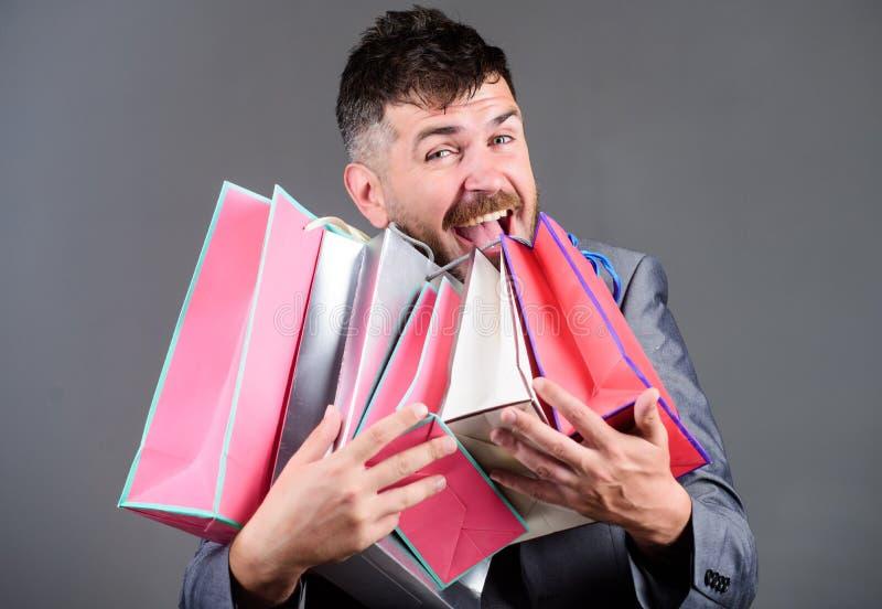 Shopping tour di soddisfazione Il cliente barbuto dell'uomo d'affari dell'uomo porta molti sacchetti della spesa Acquisto con lo  immagine stock
