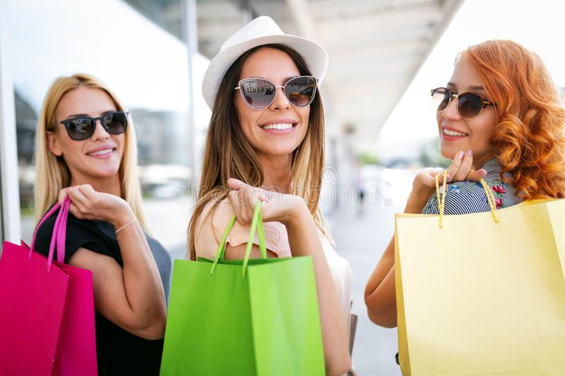 Shopping, fun and tourism concept. Beautiful girls with shopping bags in ctiy stock photos