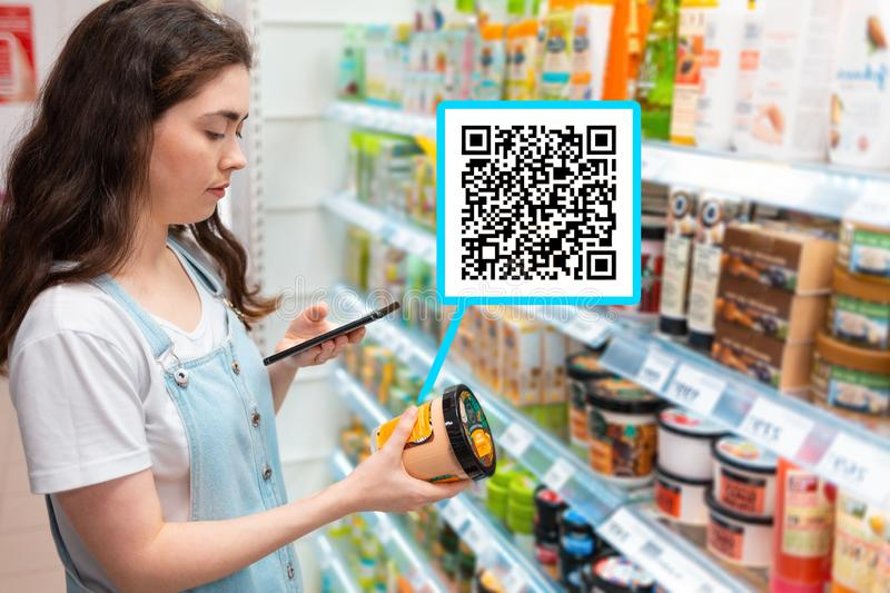 Shopping trip. Young beautiful woman scanning body cream advertisement with quick response code on mobile smartphone. Close up royalty free stock image