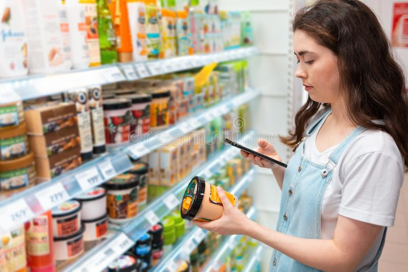 Shopping trip. Young beautiful woman taking pictures of a jar of cream in a cosmetics store royalty free stock photography