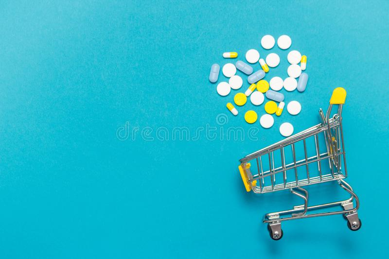 Shopping trolley cart with assorted medicine pills one blue background. Creative idea for drugstore, online pharmacy, health stock photo