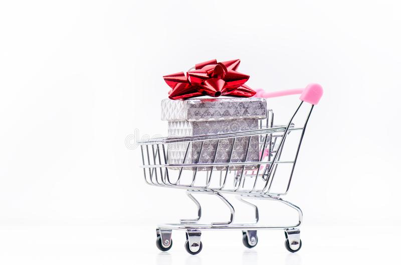 Shopping trolley with christmas gift. Gift box with red ribbon isolated on a white background. Christmas decoration. stock photos