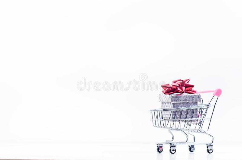 Shopping trolley with christmas gift. Gift box with red ribbon on a white background. Christmas decoration. stock image