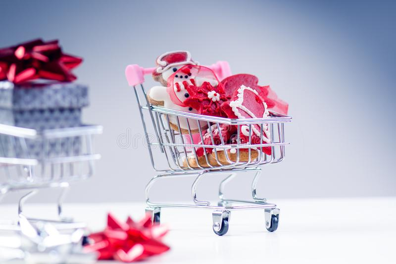 Shopping trolley with christmas gift. Gift box with red ribbon on a white background. Christmas decoration. royalty free stock photography