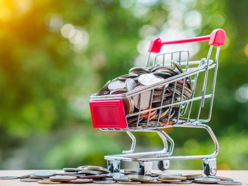 Shopping trolley with coins. saving money, spend money for shopping concept. stock image