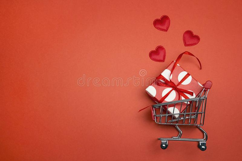 Shopping trolley with gift box, love hearts and cope space royalty free stock photography
