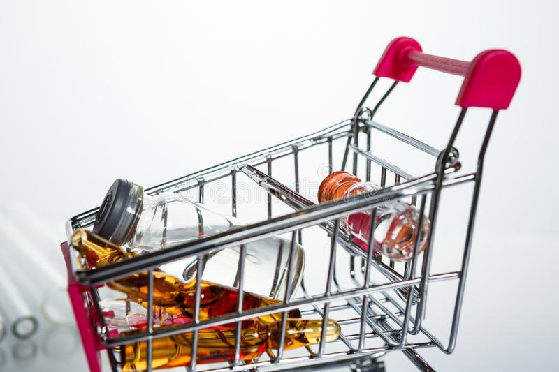Shopping trolley with injection needle and medicine bottles. Healthy and medical concept royalty free stock photography