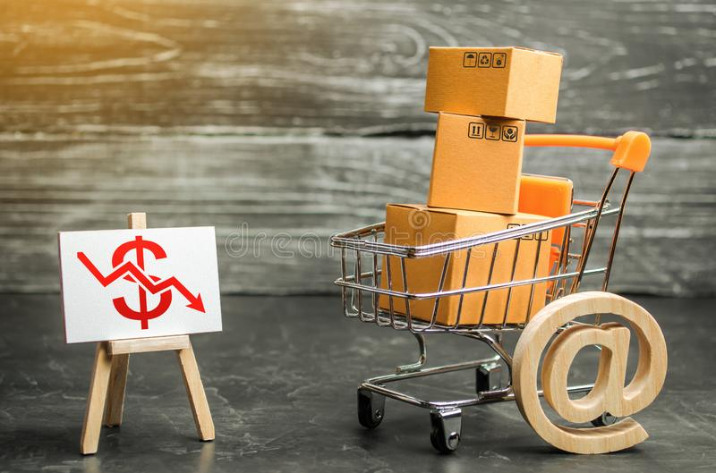 A shopping trolley loaded with boxes and an easel with a red dollar down arrow. Internet trade, online purchase. Drop in sales. Economic recession. Retail of royalty free stock photography
