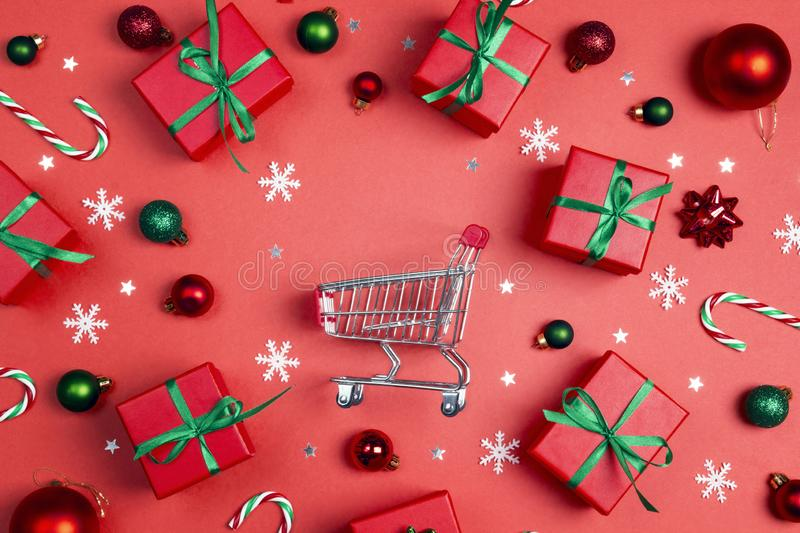 Shopping trolley with red gift boxes and copy space on a red background royalty free stock photos