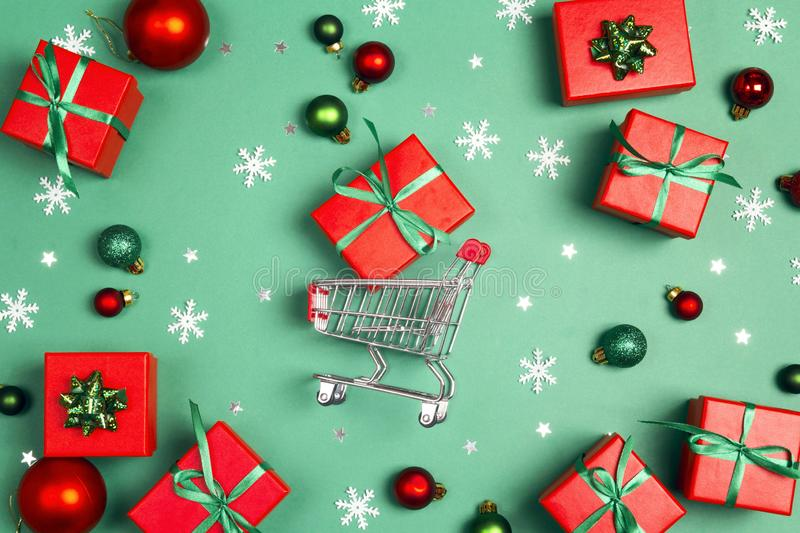 Shopping trolley with red gift boxes on a green background stock photography