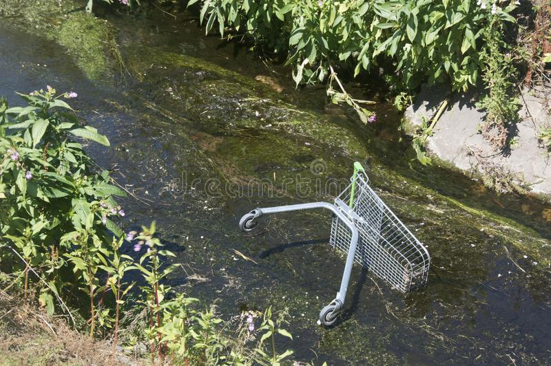 Shopping trolley in river stock photography