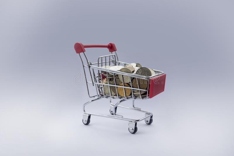 Coins in shopping cart. Banking and marketing. Shopping trolley with small coins. Red basket with coins on grey background. Shopping for the holiday. lack of royalty free stock photos