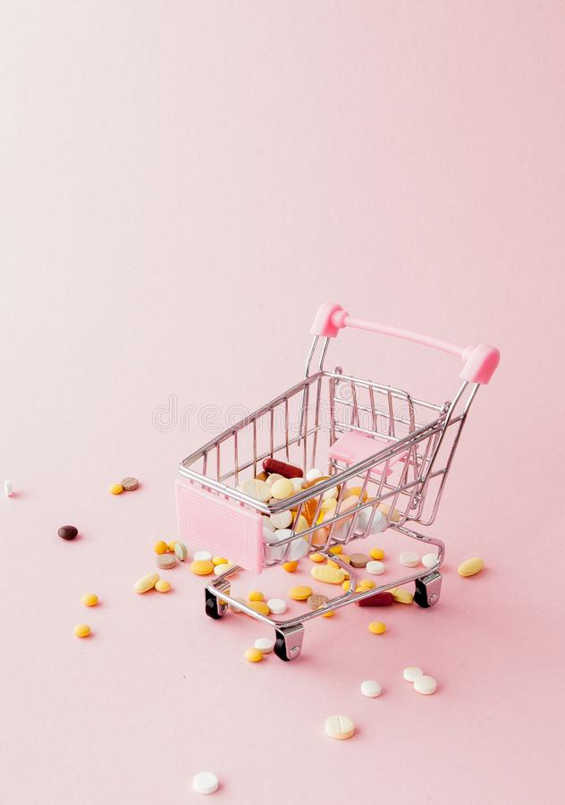 Shopping trolley from the supermarket full of pills and drugs on a pink background. Purchases of medical preparations, purchase on stock photos