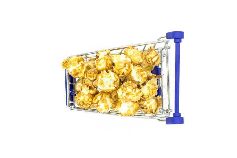 Shopping trolley toy full of popcorn on white background minimal concept. Top view royalty free stock photo