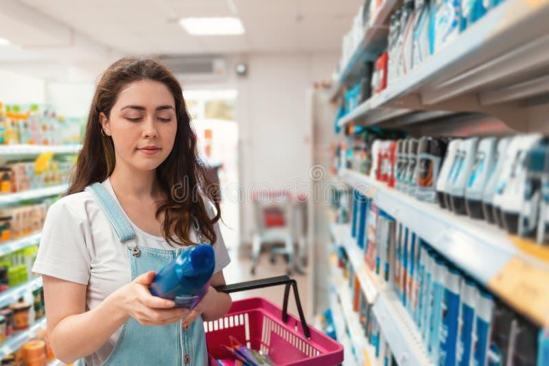 shopping Ung härlig kvinna som läser en etikett av schampo i lagret arkivfoton