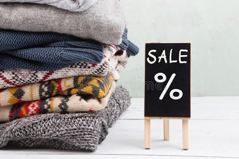 Shopping for gifts - warm sweaters and sale signboard. Shopping - warm sweaters and sale signboard royalty free stock image