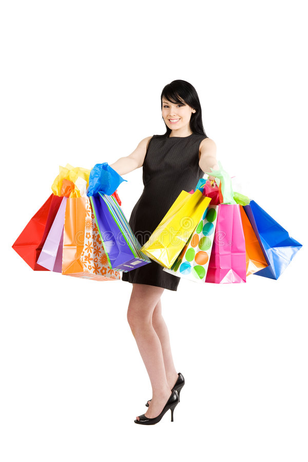 Shopping woman. An isolated shot of a beautiful woman carrying shopping bags royalty free stock images