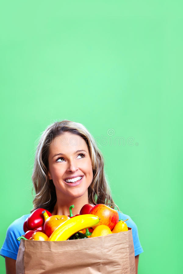 Shopping woman with a bag of food. Smiling young woman holding a shopping bag with food stock images