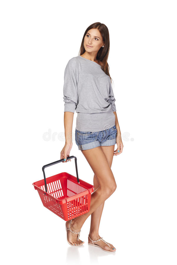 Shopping woman. Full length casual young woman standing with empty shopping cart basket and looking away at blank copy space, over white background stock image