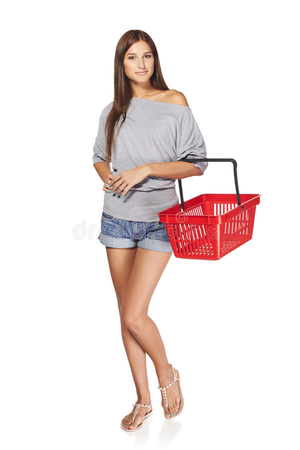 Shopping woman. Full length casual young woman standing smiling with empty shopping cart basket, over white background royalty free stock photo