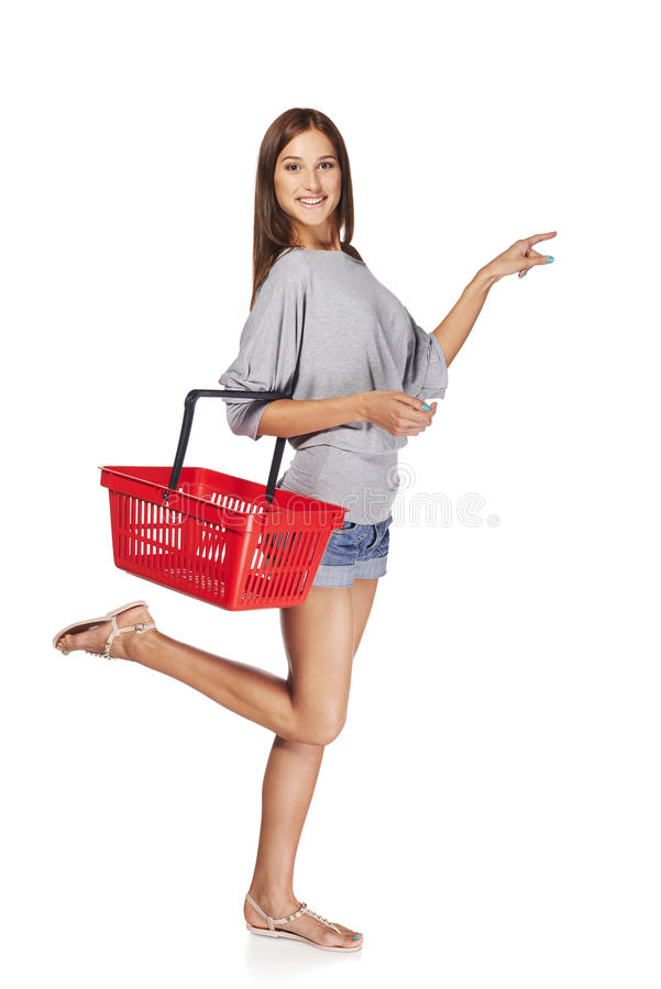 Shopping woman. Full length excited casual young woman with empty shopping cart basket pointing finger at blank copy space, over white background royalty free stock photo