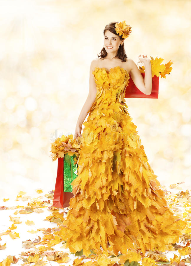 Shopping Woman Happy In Autumn Fashion Dress Of Ye. Llow Fall Leaves With Paper Bags, Girl Spree Walking After Autumnal Clearence Sale in Shopping Mall royalty free stock photos