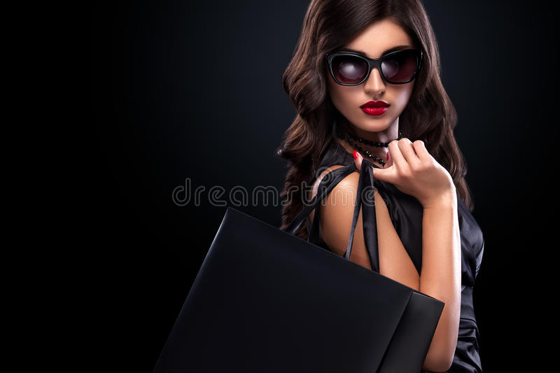 Shopping woman holding grey bag isolated on dark background in black friday holiday. Beautiful young woman make shopping in black friday holiday. Girl with black
