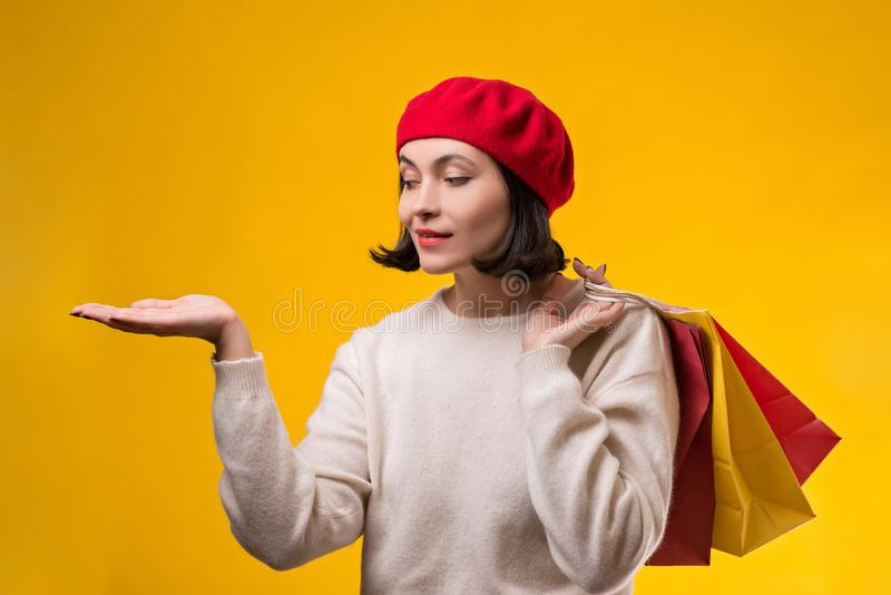 Shopping woman showing something with open hand palm. Happy girl holding shopping bags. Fashion woman shopper isolated on yellow royalty free stock images