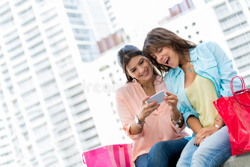 Shopping women with a cell phone