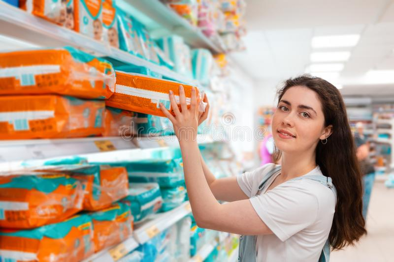 Shopping. Young beautiful woman pulls a pack of diapers from the top shelf stock photos