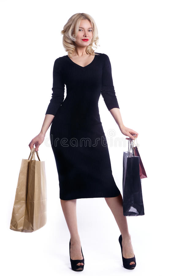 Shopping young woman holding bags isolated on white studio background. Love fashion and sales. Happy blond girl in black luxury gl stock images