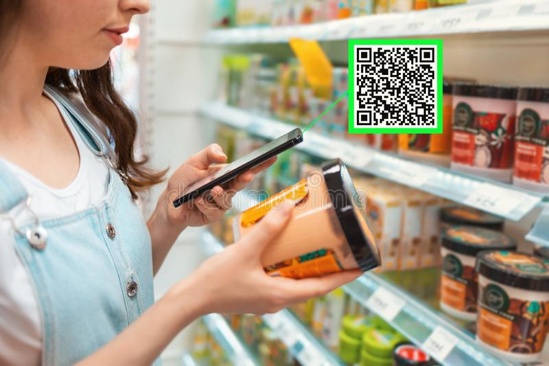 Shopping. Young woman scans qrcode of the body cream. Modern technology in everyday life. Close up.  stock images