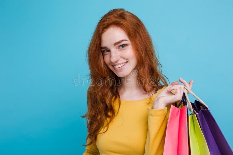 Shoppingbegrepp - ung härlig attraktiv redhairflicka för nära övre stående som ler se kameran med shoppingpåsen royaltyfri fotografi