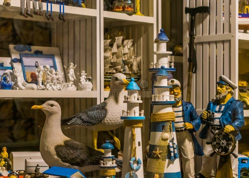 Shoppingfönstret av en strandsouvenir shoppar, skulpturer av fyrar, seagulls och sjömän arkivbild