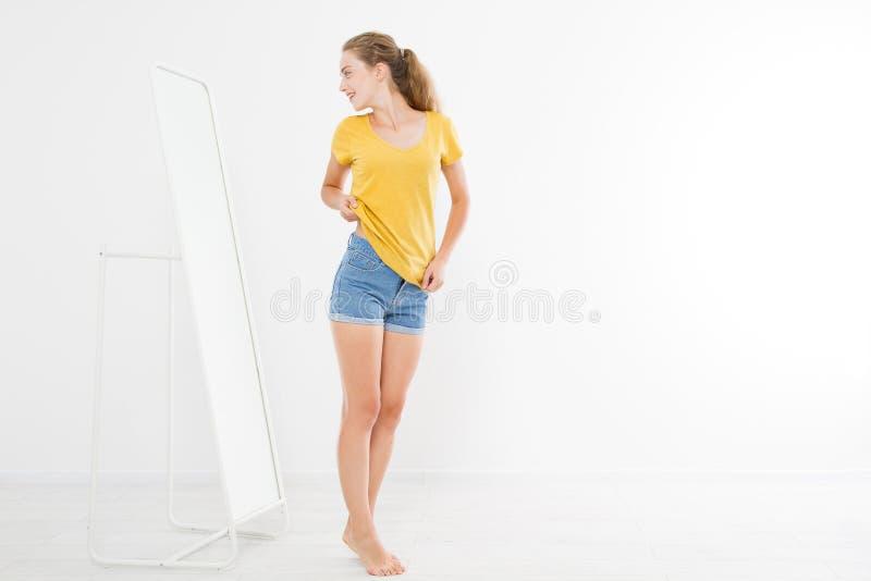 Shoppingförsäljningsbegrepp Blond flicka i jeans och t-skjorta Den unga kvinnan i bra kroppform som ser spegeln och, förlorar vik royaltyfri fotografi