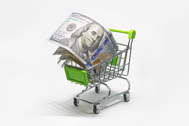 Shoppingkorg med dollarsedlar, räkningar som isoleras på vit bakgrund arkivfoton