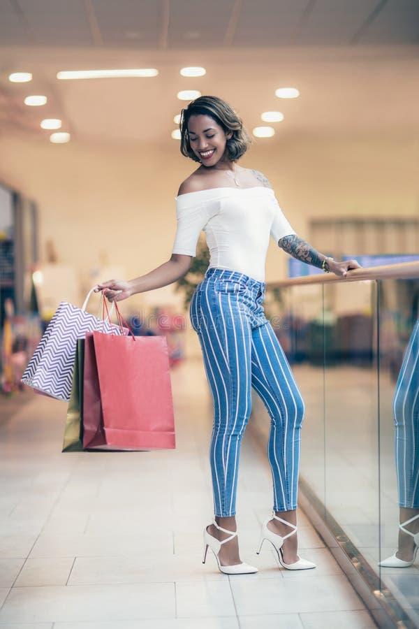 Shoppingkvinna som ler och rymmer påsar i shoppinggalleria royaltyfria foton