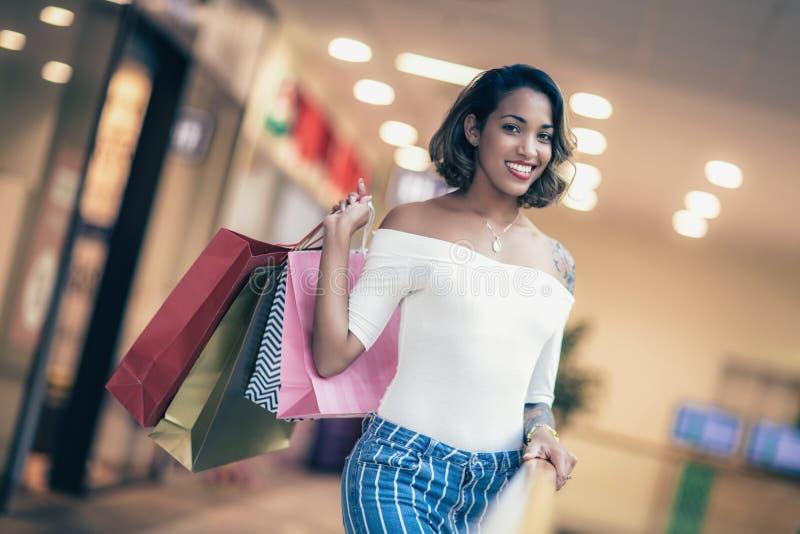 Shoppingkvinna som ler och rymmer påsar i shoppingmor royaltyfri fotografi