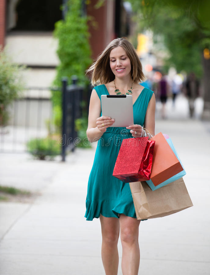 Shoppingkvinna som rymmer den Digital minnestavlan royaltyfri foto