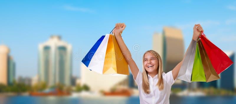 Shoppingkvinna som rymmer shoppingpåsar ovanför hennes huvud som ler under försäljningsshopping över Dubai stadsbakgrund royaltyfri bild