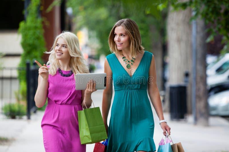 Shoppingkvinnor med den Digital minnestavlan royaltyfria bilder