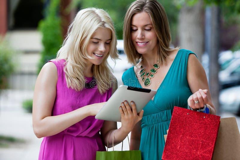 Shoppingkvinnor som använder den Digital minnestavlan royaltyfria bilder