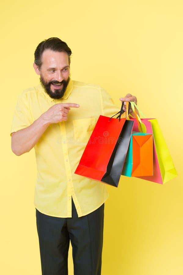 Shoppinglycka Emotionellt tyckande om shoppa för man Skäggig mogen man med shoppingpåsen på gul bakgrund Sale och arkivfoto
