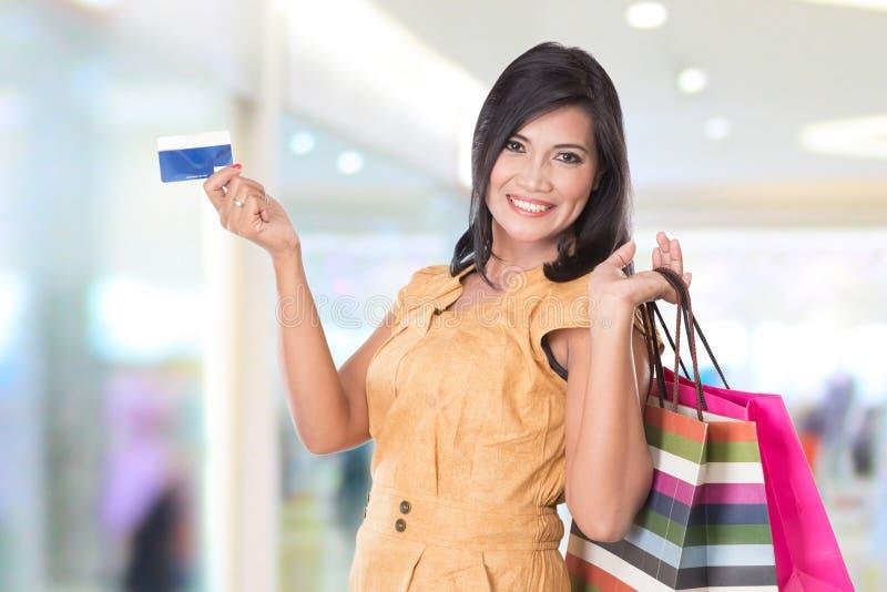 Shoppingpåsar och kreditkort för lycklig asiatisk kvinna hållande royaltyfria foton