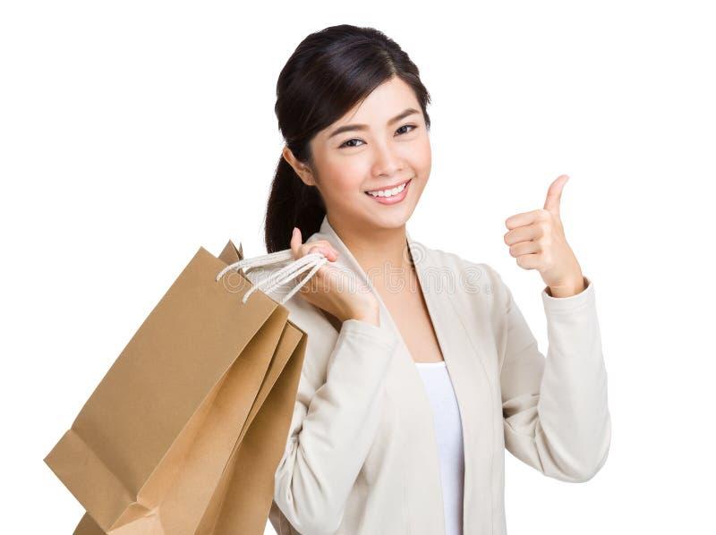 Shoppingpåse och tumme för asiatisk kvinna hållande upp royaltyfri fotografi