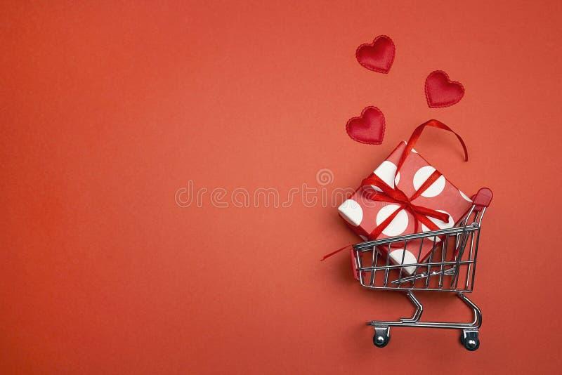 Shoppingspårvagn med gåvaasken, förälskelsehjärtor och korkåpautrymme royaltyfri fotografi
